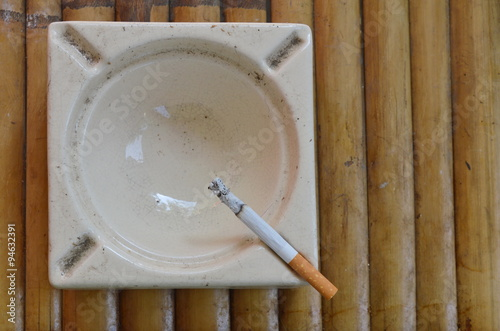 Fotografie, Obraz  cigarette in tile ash tray on bamboo