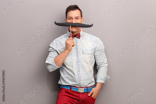 Photo  Cheerful young man with a huge fake moustache