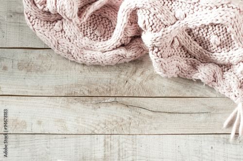 Fotografie, Obraz  pink knitted scarf on wooden board with copy space for text.