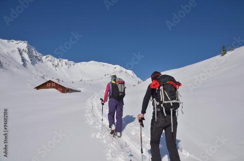 Poster Wintersporten Beim Aufstieg auf Skitour mit Sicht auf Hütte und Gipfel