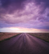 sunset in cloudy sky over road