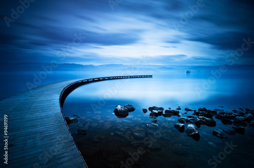 Blue sea and curve jetty Canvas Print