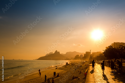 Fototapeta Unidentifiable silhouettes enjoy late afternoon sun rays on Ipanema beach in Rio de Janeiro, Brazil.  Ipanema is one of the most expensive places to live in Rio, obraz