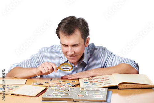 Fotomural Man watching a collection of postage stamps with magnifier