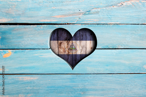 Stampa su Tela Love Nicaragua. Heart and flag on a blue wooden board