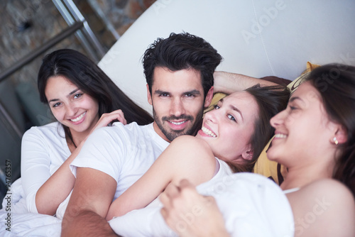 Fotografía  handsome man in bed with three beautiful woman