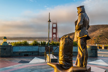 Lone Sailor Memorial Statue, Sausalito, CA, And View Of The Golden Gate Bridge During Sunrise