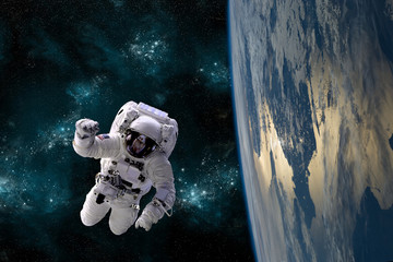 Obraz na Szkle Kosmos An astronaut floats in the zero gravity environment of space - Elements of this image furnished by NASA.