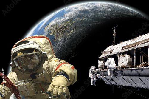 Fotografia, Obraz  A team of astronauts and cosmonauts perform work in space - Elements of this image furnished by NASA