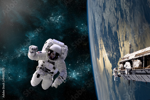 Fotografia, Obraz  A team of astronauts perform work on a space station - Elements of this image furnished by NASA
