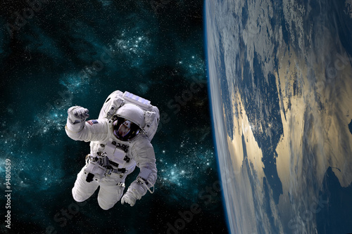 Fotografia, Obraz  An astronaut floats in the zero gravity environment of space - Elements of this image furnished by NASA
