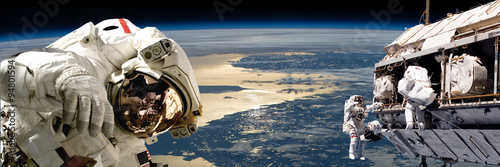 Deurstickers Heelal A team of astronauts performing work on a space station.- Elements of this image furnished by NASA.