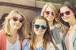 Vier junge Frauen mit Sonnenbrille posieren