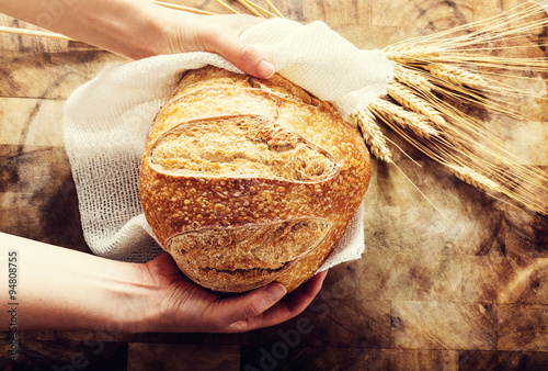 Spoed Foto op Canvas Brood Baker holding a loaf of bread on rustic bacgkround
