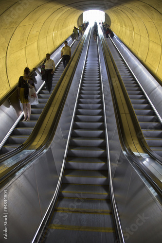 An escalator with passengers moves through oval tube of light to the Washington D Wallpaper Mural