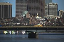 Yellow Taxi Drives Across Harvard Bridge Over Charles River With Colorful Sailboats, Boston, Massachusetts, USA, 03.18.2014