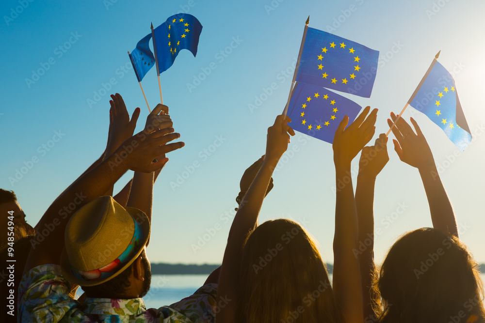Fototapeta People with raised hands waving flags of the European Union.
