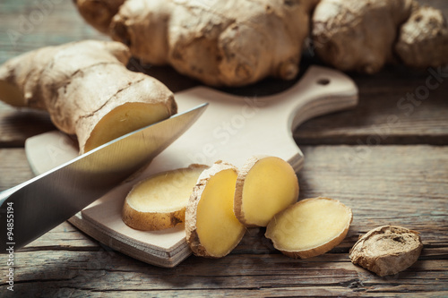 Obraz na płótnie Chopped ginger root on cutting board on rustic wooden rustic tab