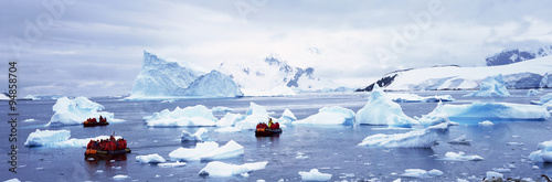 Poster Antarctique Panoramic view of ecological tourists in inflatable Zodiac boat with glaciers and icebergs in Paradise Harbor, Antarctica
