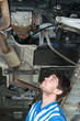 Mechanic examining the exhaust of a car