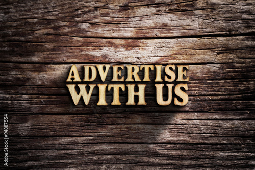Fotografía  Advertise with us. Words on old wooden board.