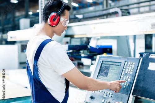 Fotografie, Obraz  Pracovník zadávání dat do CNC stroji ve výrobním závodě