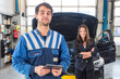 Proud mechanic, posing in front of a client with her car