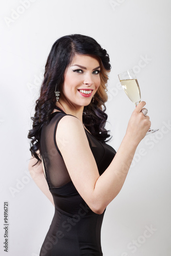 Fototapeta Beautiful young woman celebrating with a glass of champagne obraz na płótnie
