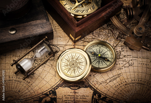 Photo  Old compass, astrolabe on vintage map. Retro stale.