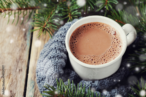 Poster Chocolate Cup of hot cocoa or hot chocolate on knitted background with fir tree and snow effect, traditional beverage for winter time