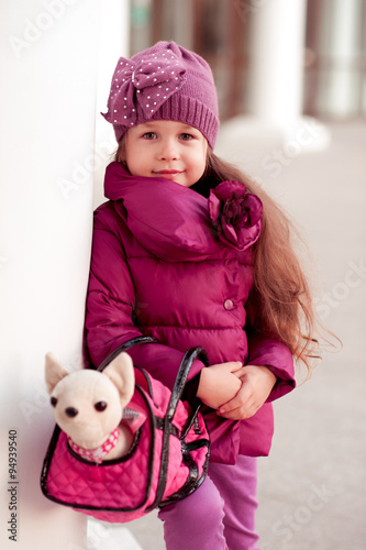 Stickers pour portes Panda Smiling baby girl 4-5 year old posing outdoors. Looking at camera. Wearing stylish winter jacket and knitted hat. Playing with dog toy.