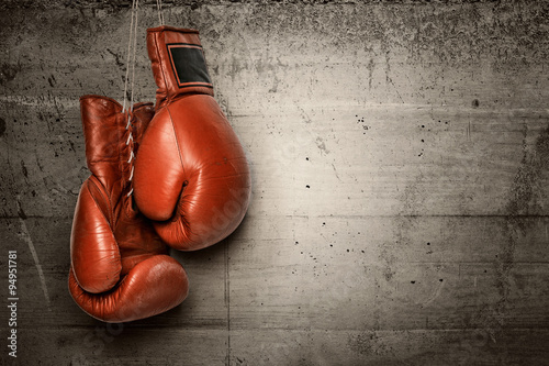 Boxing gloves hanging on concrete wall