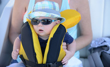 Baby With Lifejacket On That Needs To Be Zipped Up With Sunglass