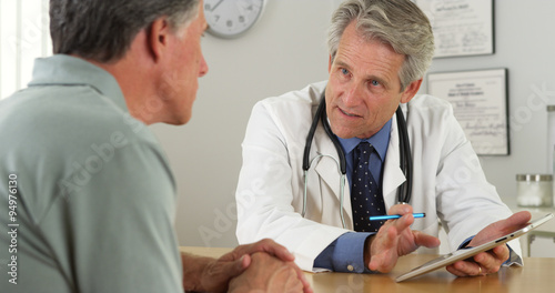 Fotografia  Senior doctor talking with patient and tablet in office
