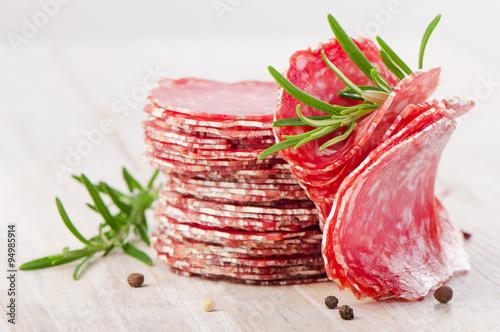 Fototapeta Slices of salami sausage on a wooden table. obraz