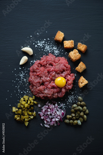 Beef steak tartare over black wooden surface, above view Canvas Print