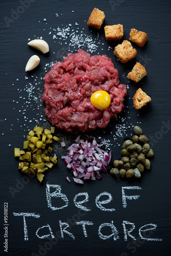 Above view of beef steak tartare on a black wooden background Canvas Print