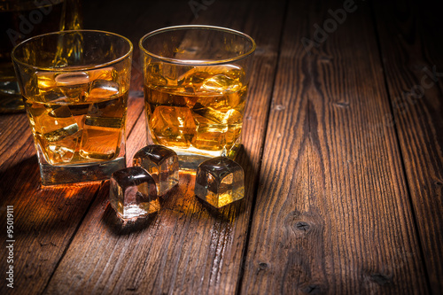 Photo  Two glasses of whiskey with ice on wooden table