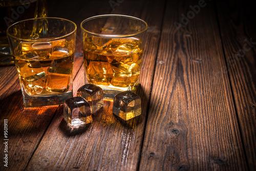 Fotografía  Dos vasos de whisky con hielo en la mesa de madera
