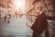 canvas print picture - Portrait of beautiful young woman standing on the street and using her mobile phone