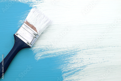 Paintbrush with white paint painting over blue