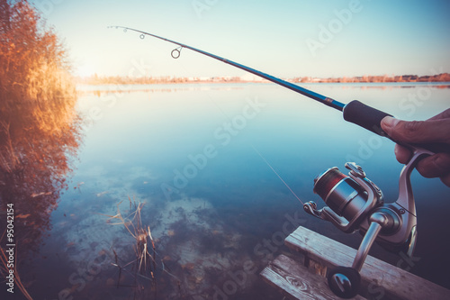 Papiers peints Peche hand with spinning and reel on the evening summer lake