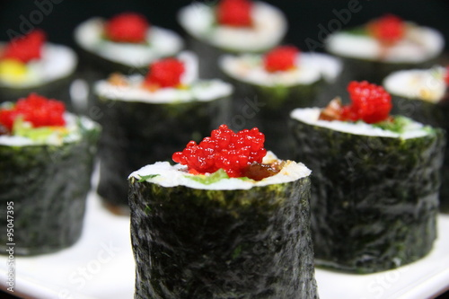 Fresh made sushi made with a maki roll and fish eggs on top