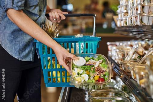 Fotografie, Obraz  a woman buying a salad at a deli