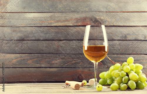 kieliszek-bialego-wina-i-zielonych-winogron-na-drewnianym-b