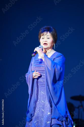 Fotografía  ステージの上でドレスを着て歌うシニア女性