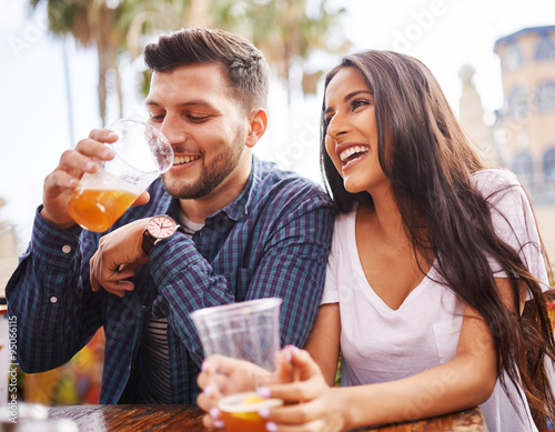 hispanic couple drinking beer on date together at outdoor patio Fototapete