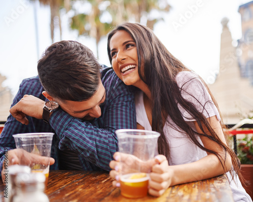 Fényképezés hispanic couple laughing and having fun while drinking beer