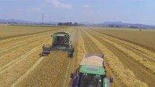 AERIAL: Loaded Tractor With Wheat Drives Away From Combine