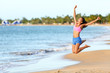 Excited woman jumping at beach. Cheerful female in sportswear is enjoying on shore. Runner with arms raised screaming in midair on sunny day.